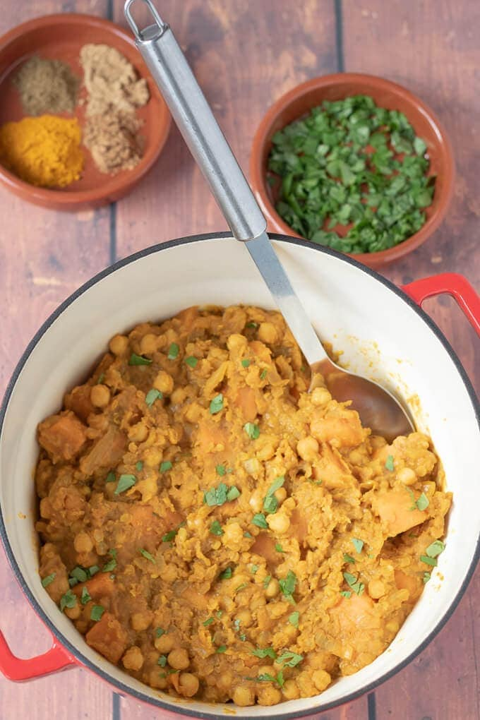 Moroccan lentil stew shown made in a large casserole pot with a serving spoon. Ready to serve.