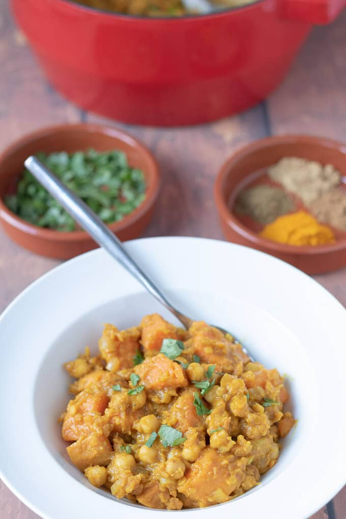 Delicious Moroccan lentil stew served in a white bowl with a fork in it and ready to eat. Spiced and a dish a freshly chopped coriander in the background.