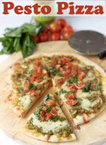 Pesto pizza cooked sitting on a chopping board with a slice carved out.Cherry tomatoes and basil in the background for decoration. Pin title text overlay at top.