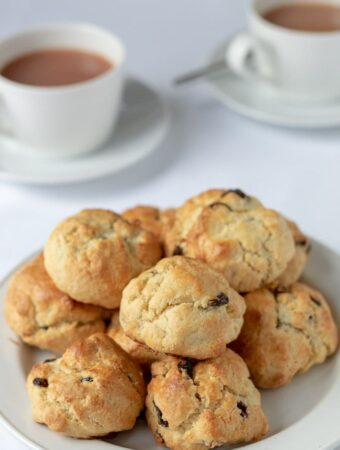 Rock cakes in a pile on a plate with cups of freshly pured tea in the background.