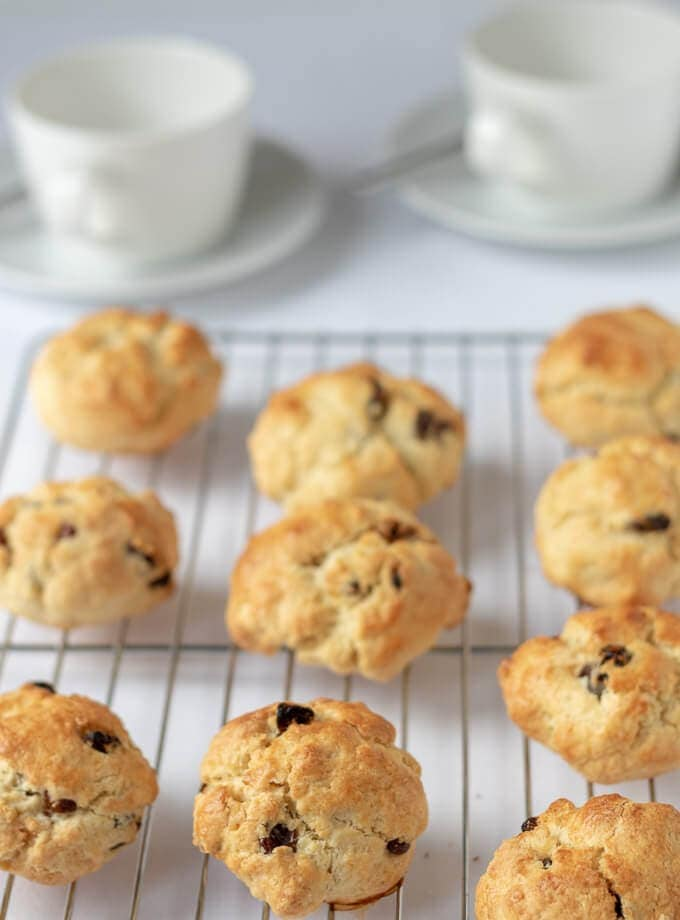 Rock cakes just taken out of the oven and cooking on a wire rack with empty tea cups in the background.