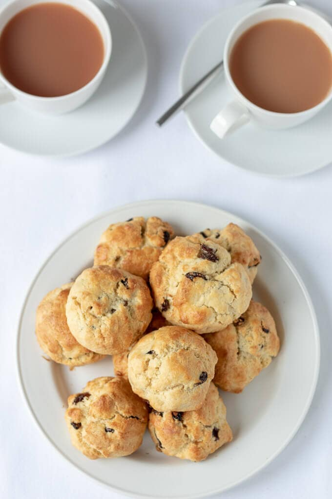 Birds eye view of a pile of rock cakes on a plate with freshly poured cups of tea above.