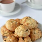 Rock cakes in a pile on a plate with cups of freshly pured tea.