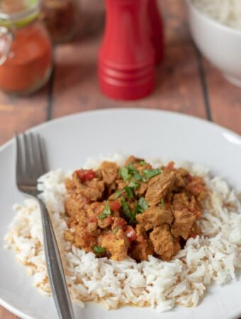 Delicious slow cooker beef curry on a plate served on a bed of rice garnished with coriander and a fork beside. SAlt and pepper cellars, a bowl of rice and spice jar in the background.
