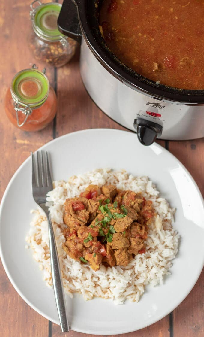 Birds eye view of a plate of slow cooker beef curry served on a bed of rice with the slow cooker in the background.