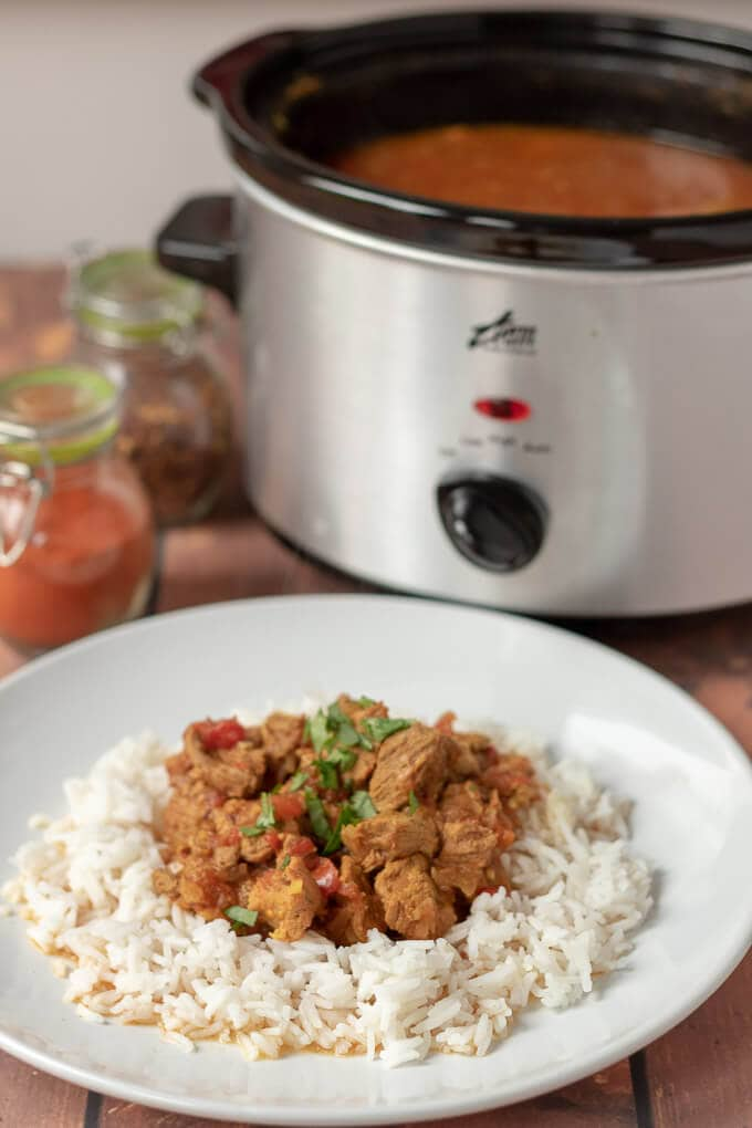 A plate of delicious cooked slow cooker beef curry served on a bed of rice with the slow cooker in the background.