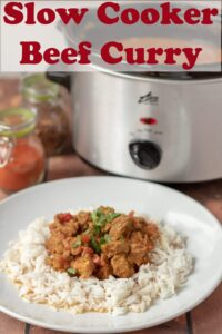 Delicious slow cooker beef curry on a plate served on a bed of rice garnished with coriander. Slow cooker in the background. Pin title text overlay at top.