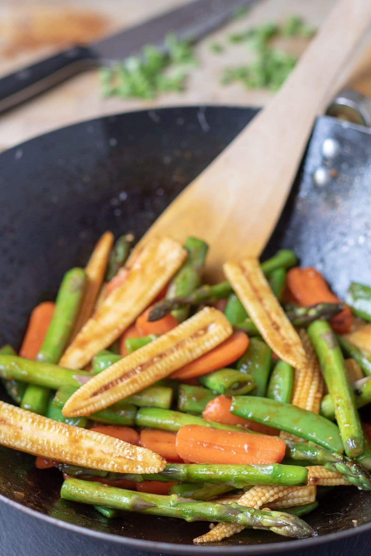 Healthy spring stir-fry vegetables in a wok and ready to serve with a wooden spatula in.