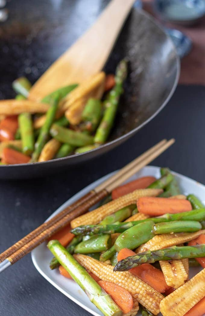 Healthy spring stir-fry vegetables being served from wok to place. Ready to eat with chopsticks.