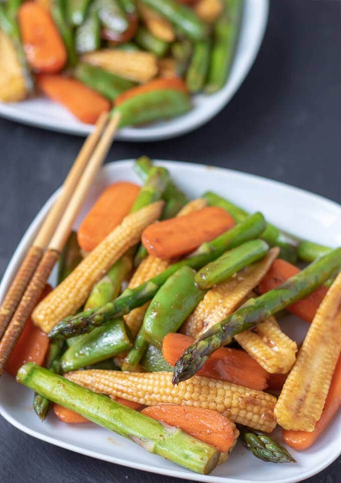 Healthy spring stir-fry vegetables served and ready to eat on two plates.