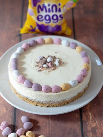 Freshly decorated easy no-bake mini egg Easter cheesecake ready to be sliced and served with a packed of mini eggs in the background.