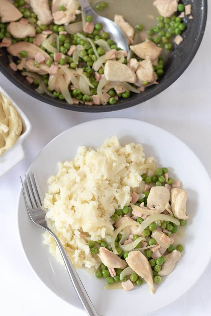 Looking down on a tasty plate of chicken with peas and bacon served with mashed potatoes with a fork placed to the side looking delicious and ready to eat. The pan with the remainder of the cooked ingredients is in the background.