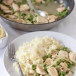 Simple chicken with peas and bacon served on a plate with creamy mashed potato with the cooking pan in the background.