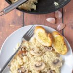 Birds eye view of a plate of this delicious 30-minute mushroom risotto served with 2 slices of garlic bread and the other half of the cooked risotto still in the pan.