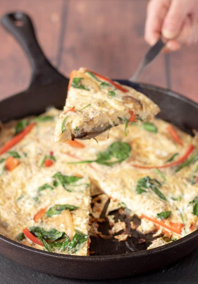 A slice of red pepper and spinach frittata being lifted from the skillet it was cooked in.