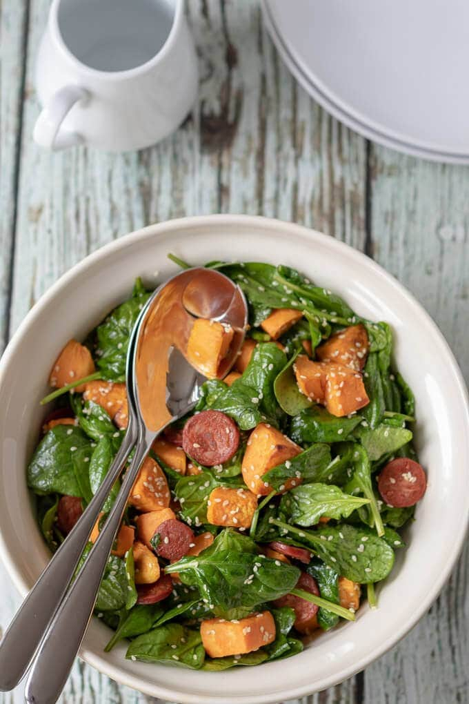 Looking top down on a bowl of chorizo and sweet potato salad with serving spoons in ready to dish onto the plates sitting beside it.