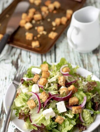 Served plate of feta and crouton salad ready to eat with a fork on the side and the tray of baked croutons in the background.