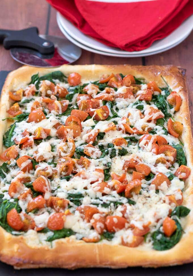 Full on view of uncut tomato cheese and spinach filo tart looking delicious and ready to serve.