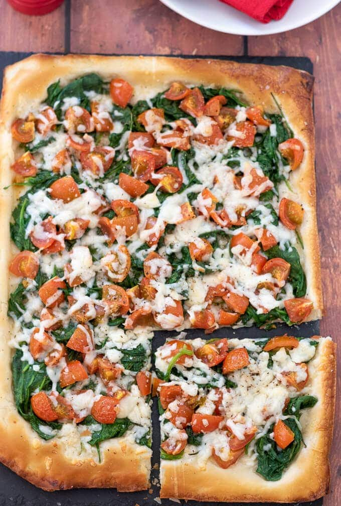 Birds eye view of tomato cheese and spinach filo tart with a square of the tart cut away at the bottom right.