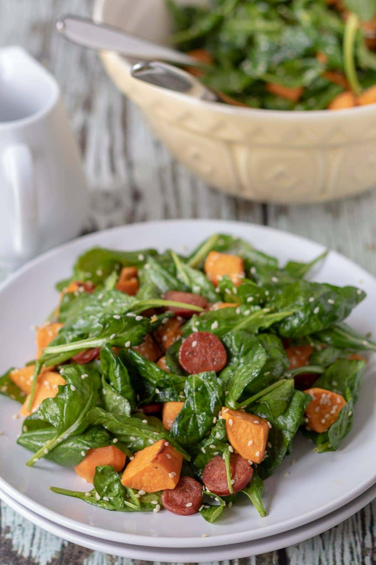 A plate of chorizo and sweet potato salad ready to eat sitting in front of a serving bowl.