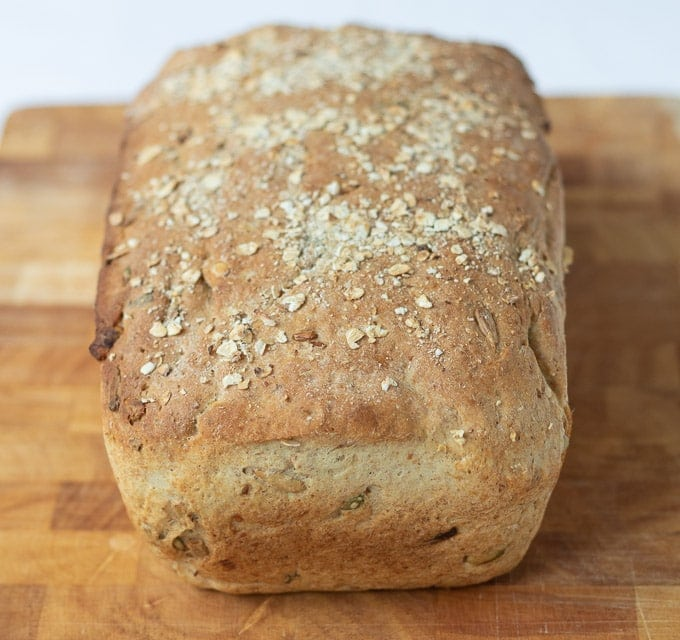 Uncut loaf of easy multigrain bread just taken out of the oven and cooling on a bread board.