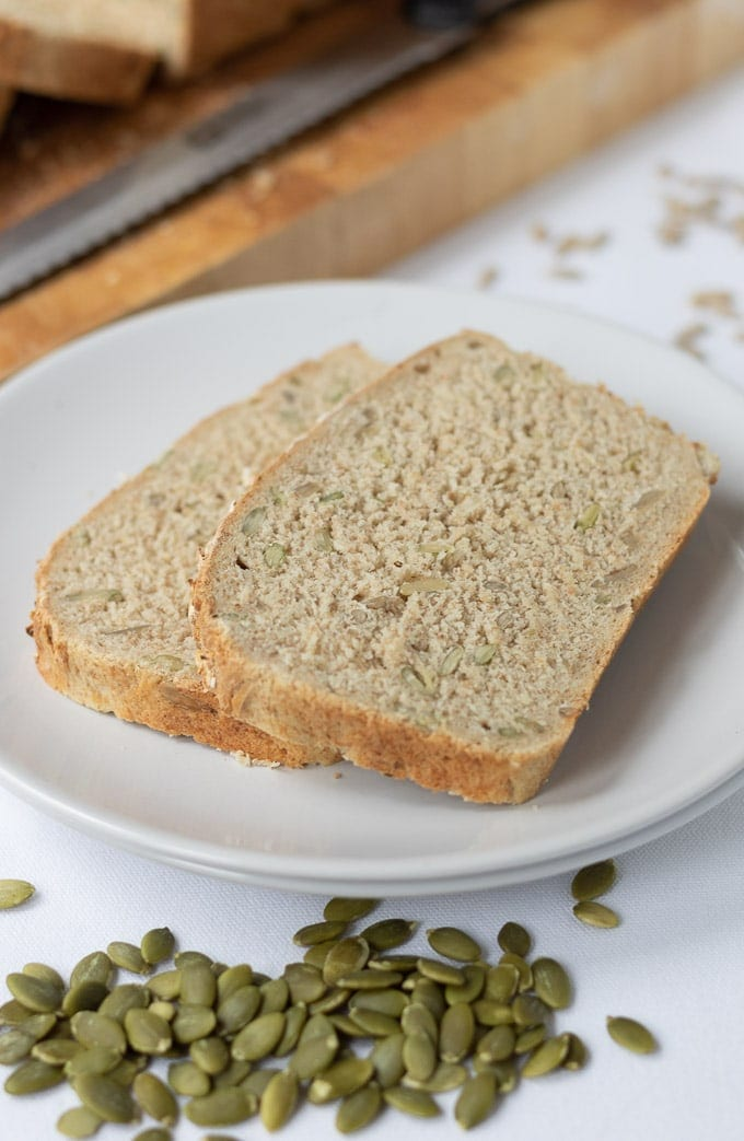 Birds eye view of two slices of easy multigrain bread on a plate with the sliced loaf at the top of the picture on a bread board.