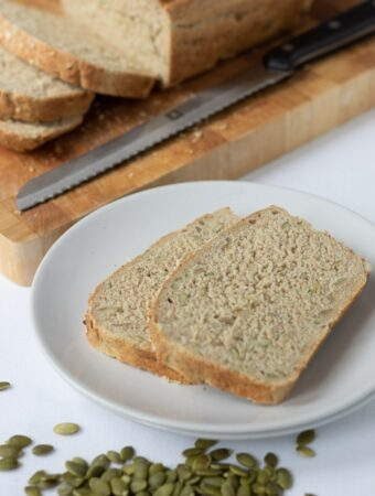 Two slices of easy multigrain bread on a plate with a scattering of pumpkin seeds in front and the cut loaf on a board in the background.
