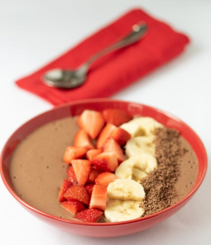 Peanut butter chocolate banana smoothie bowl decorated with chopped strawberries, sliced bananas and grated chocolate. A spoon sits on a red napkin in the background.