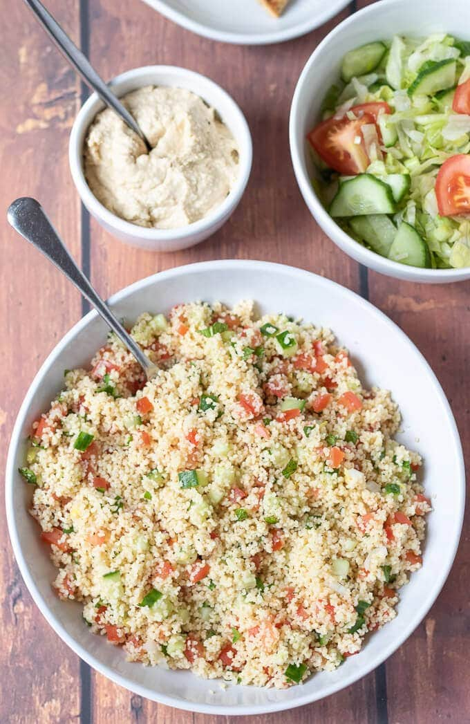 Birds eye view of a bowl of tabbouleh couscous, ramekin of hummus and bowl of side salad.