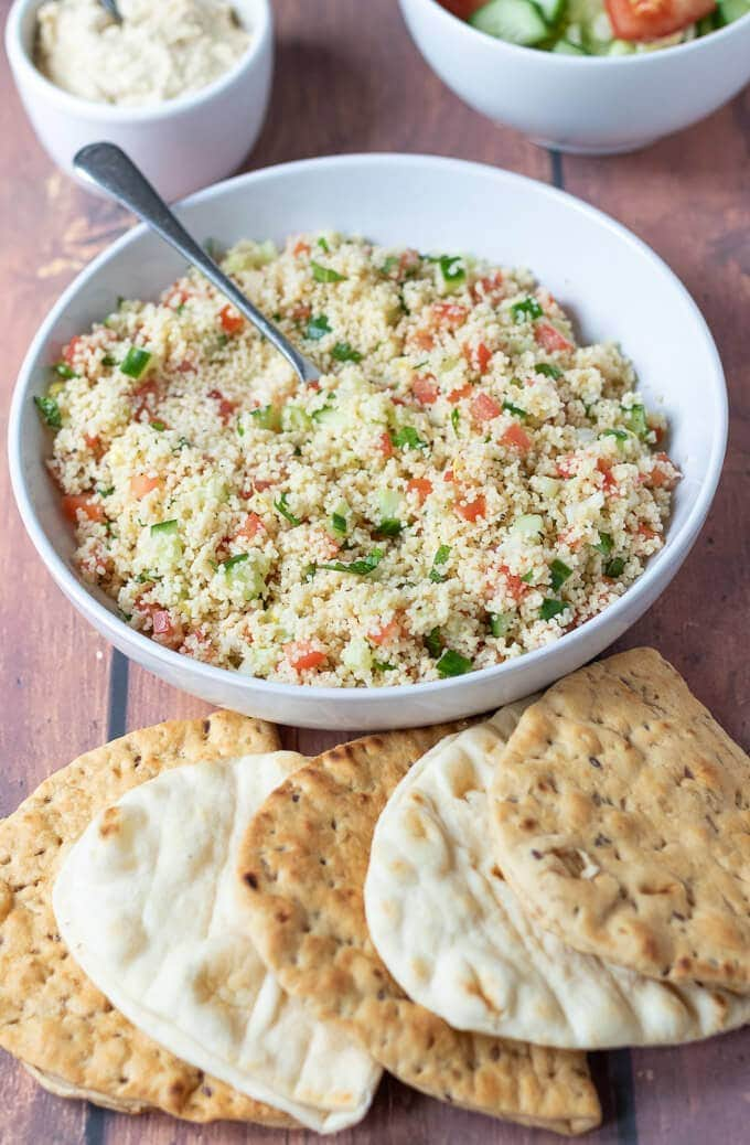 4 flat breads lie in front of a large bowl of freshly made tabbouleh couscous.