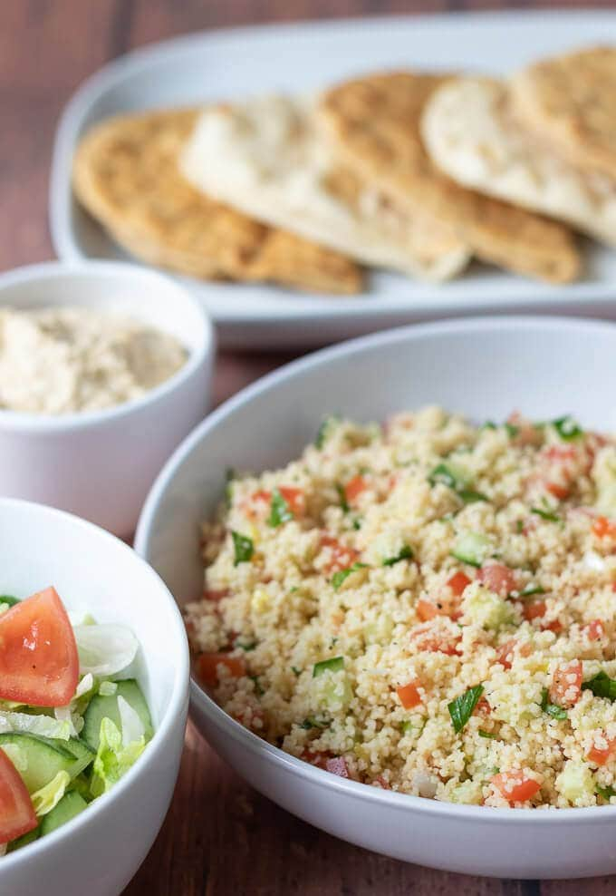 Display of main bowl of tabbouleh couscous with side salad, hummus and at the back a plate of flat breads.