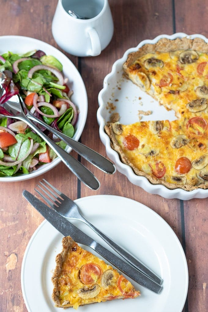 Birds eye view of a slice of tomato leek and mushroom quiche on a white plate with a knife and fork ready to eat. Quiche dish and side salad and salad dressing jug at the top of the picture.