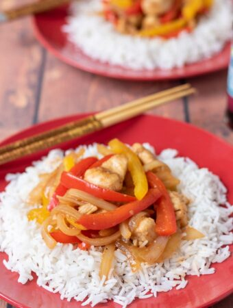 Two plates of easy sweet and sour chicken served on basmati rice one in front of the other with chopsticks on.