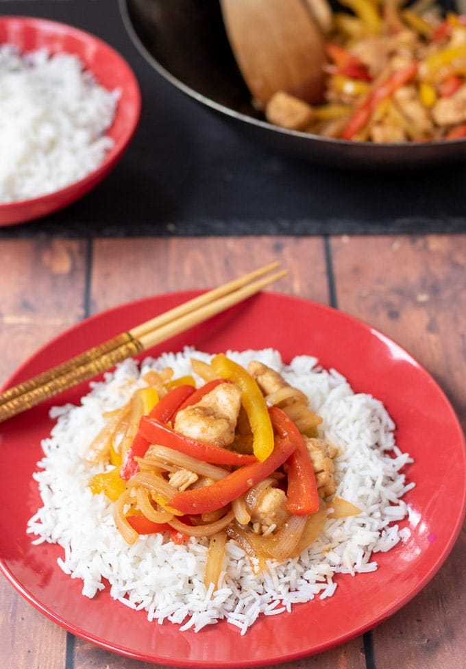 A plate of easy sweet and sour chicken served on a bed of rice with a wok and a dish of rice in the background.