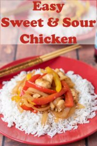 Easy sweet and sour chicken served on a bed of rice with chopsticks to the side ready to eat.