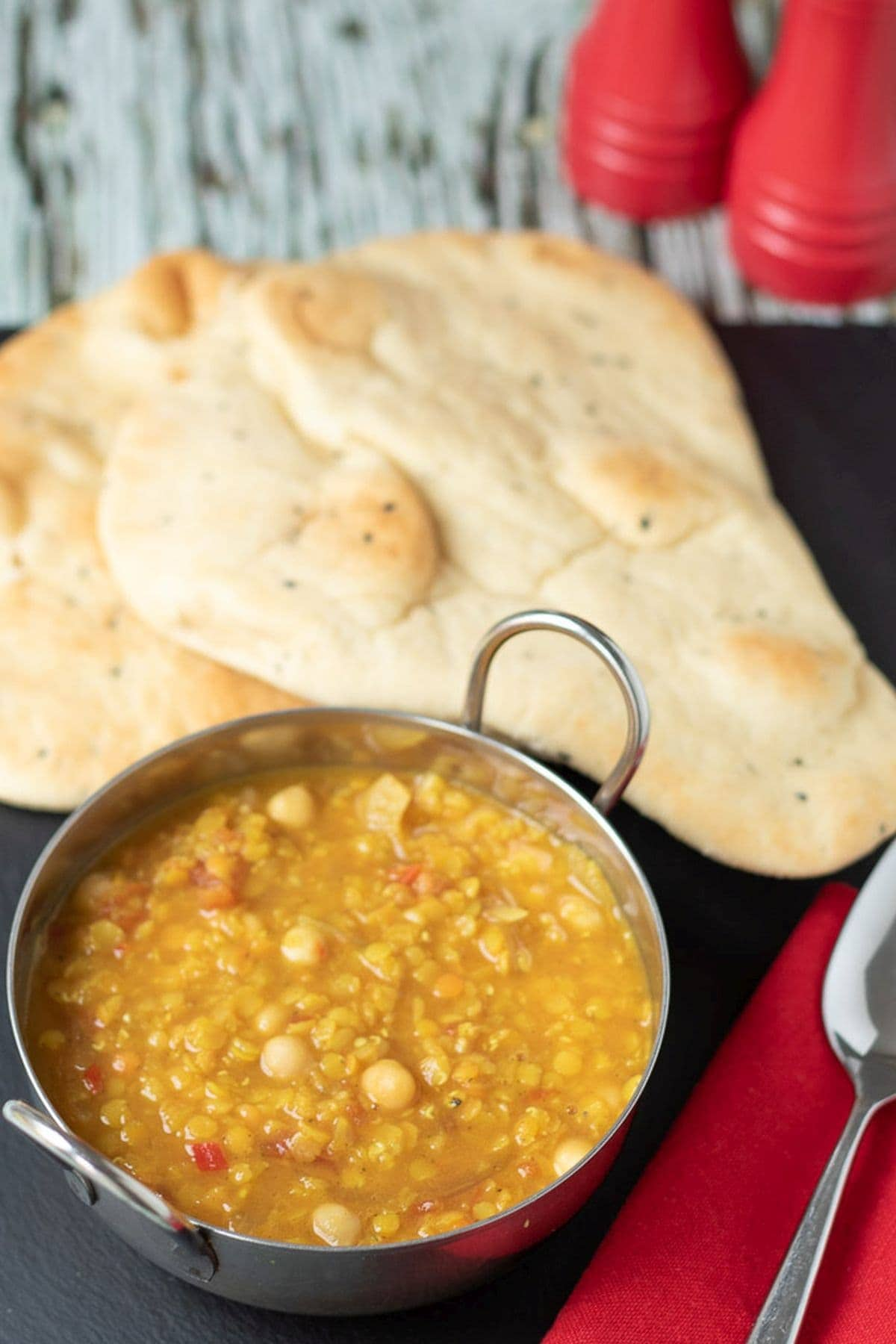 Balti dish filled with one pot chickpea and red lentil dahl with 2 naan breads in the background.