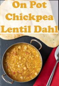 Birds eye view of a balti dish filled with one pot chickpea and red lentil dahl. Serving spoon beside. Pin title text overlay at top.