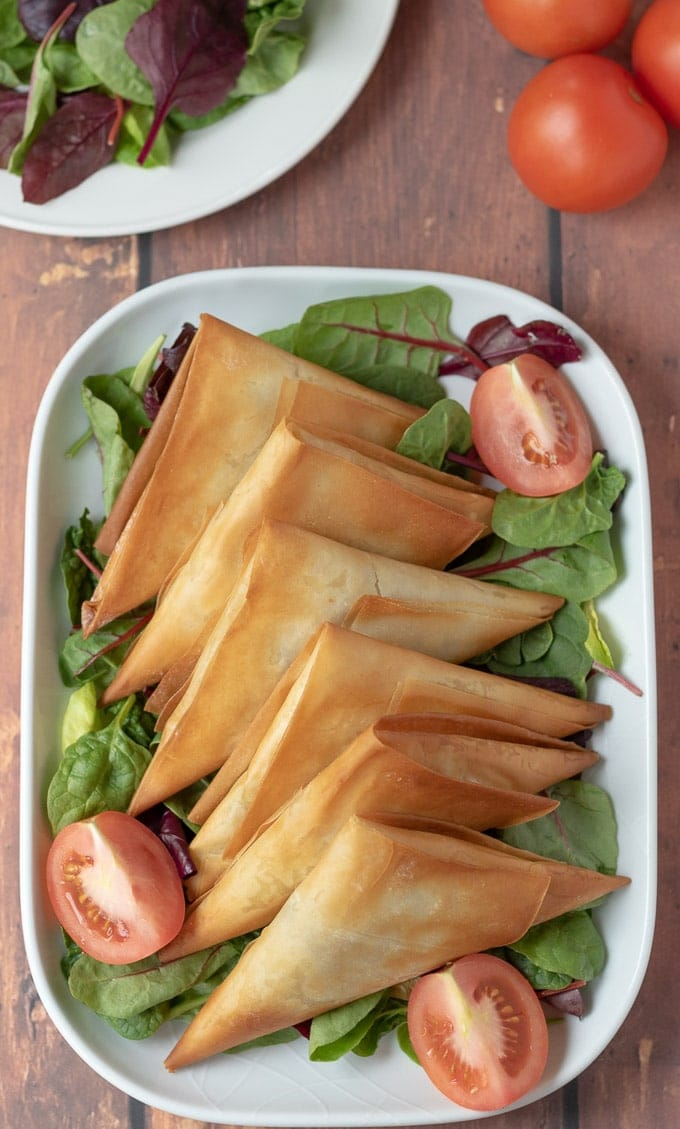 Birds eye view of roast vegetable filo parcels served on a white serving dish garnished with lettuce leaves and quartered tomatoes.