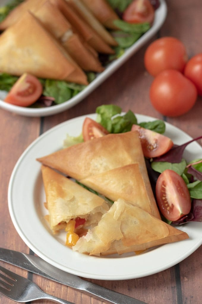 A plate of roast vegetable filo parcels and salad with one of the filo parcels cut in half with the roasted vegetable filo showing.