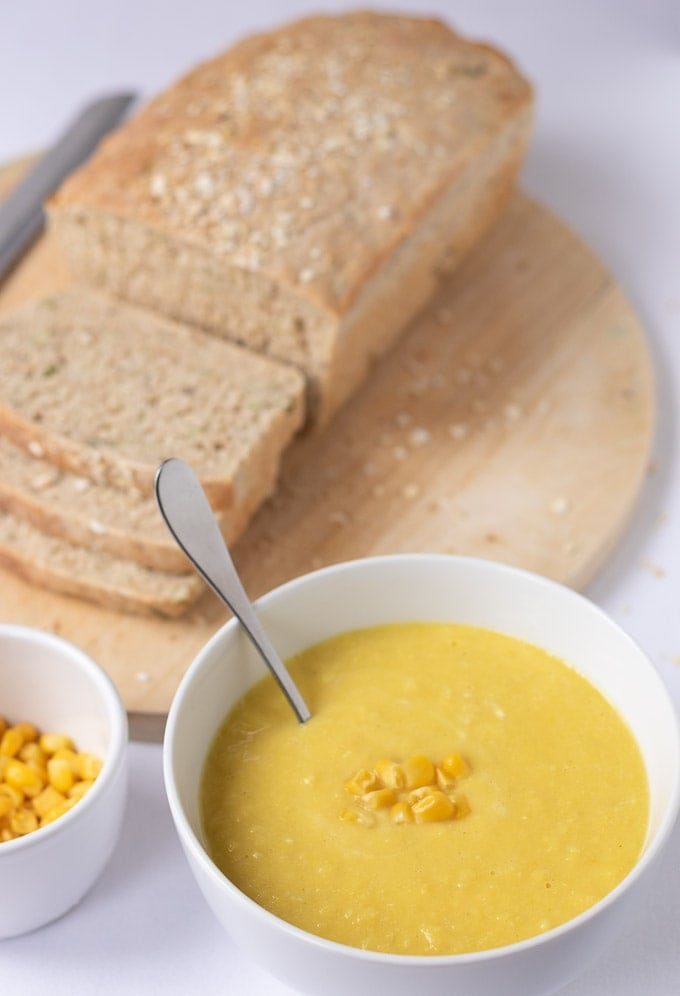 One bowl of delicious creamy 30-minute sweetcorn soup sits ready to eat with a spoon in it. Alongside is a small dish of sweetcorn to garnish and a loaf of sliced multigrain bread on a bread board.