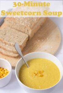 A bowl of 30-minute sweetcorn soup with a spoon in ready to eat. A cut loaf of multigrain bread to the top left. Pin title text overlay at top.