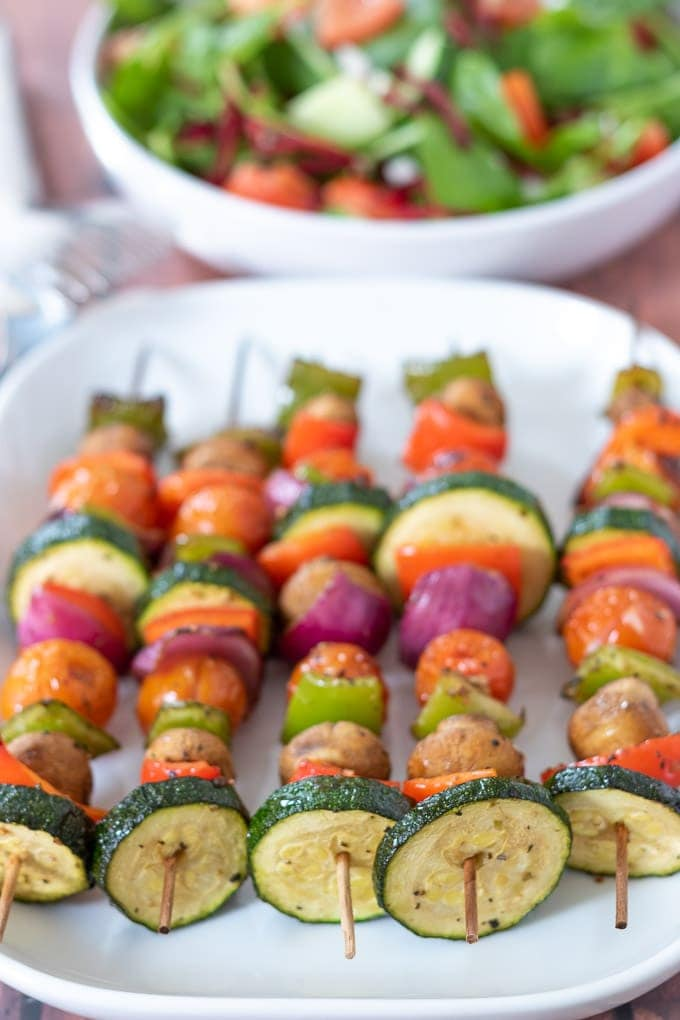 A white plate of cooked grilled vegetable skewers facing forwards with a side salad in the background.