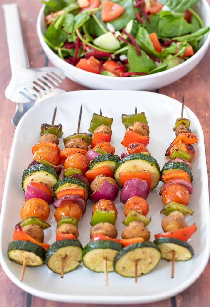 Looking down on a serving plate with 5 grilled vegetable skewers on. Side salad in the background and serving tongs to the left.