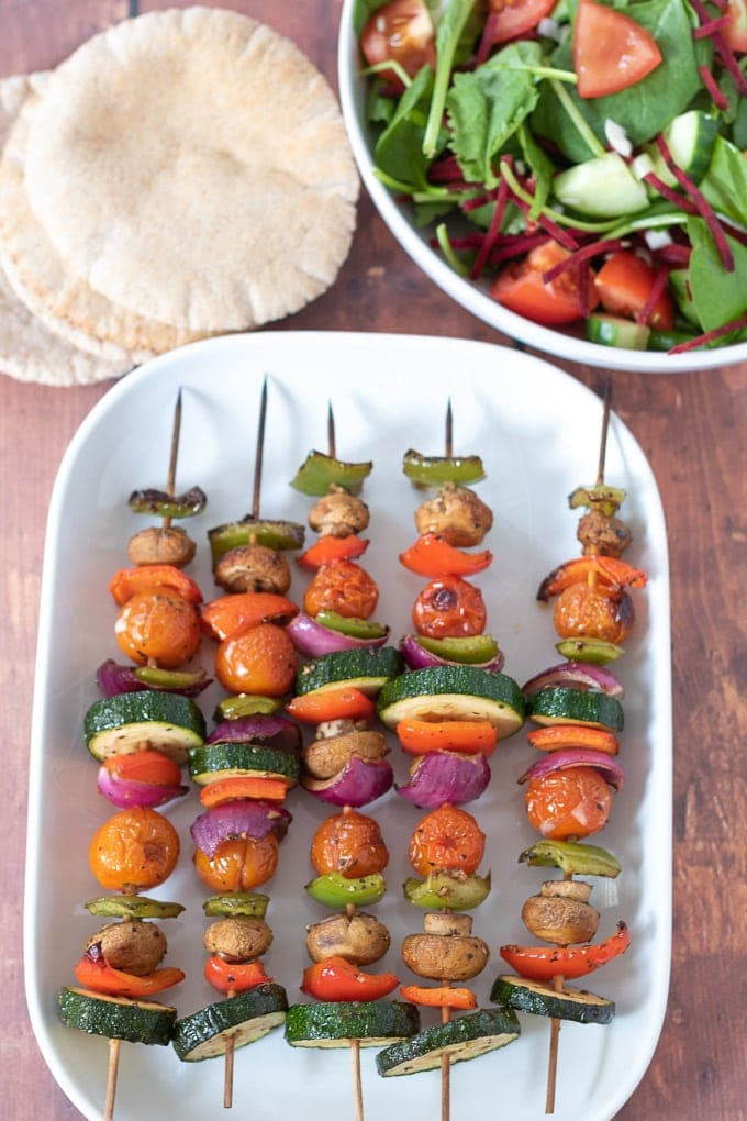 Birds eye view of 5 grilled vegetable skewers on a serving plate with 2 pita breads and a bowl of side salad at the top.