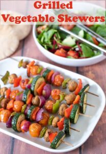 Serving dish of cooked grilled vegetable skewers with a bowl of side salad and pitta breads in the background.