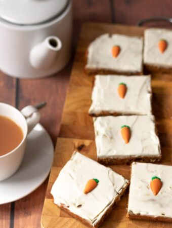 Healthy carrot cake traybake slices on a chopping board with a cup of tea and teapot to the left.