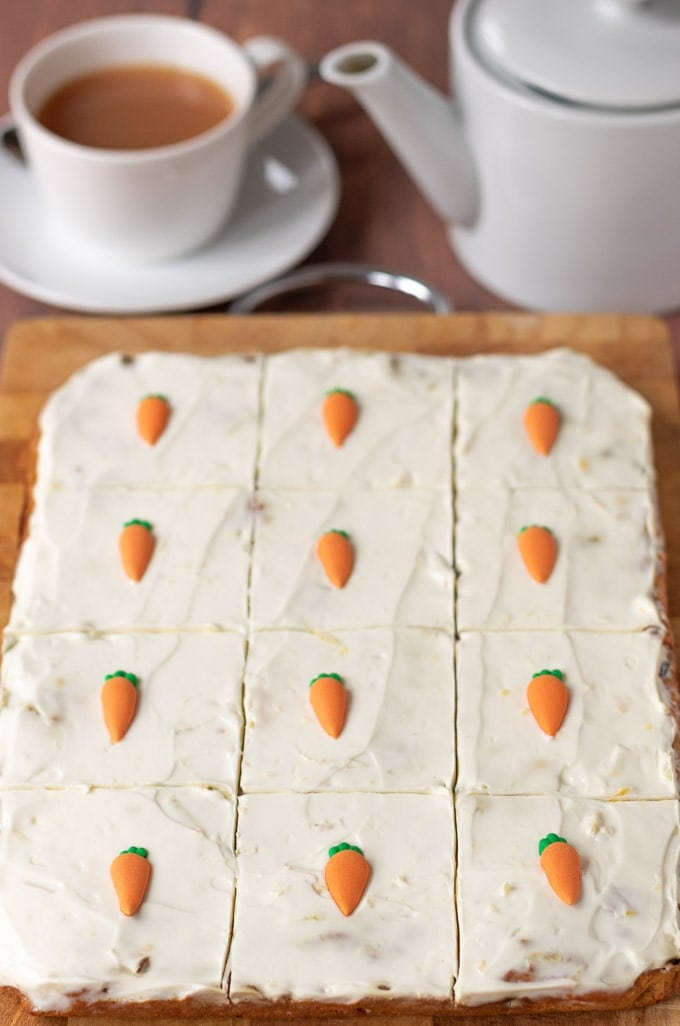 Healthy carrot cake traybake sitting on a chopping board marked into twelve slices ready to cut.