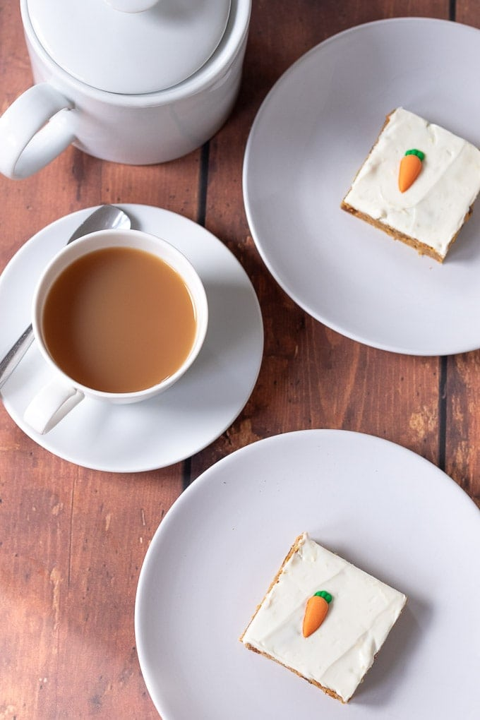 Birds eye view of two plates each with a slice of healthy carrot cake traybake on. A cup of tea and teapot to the left.