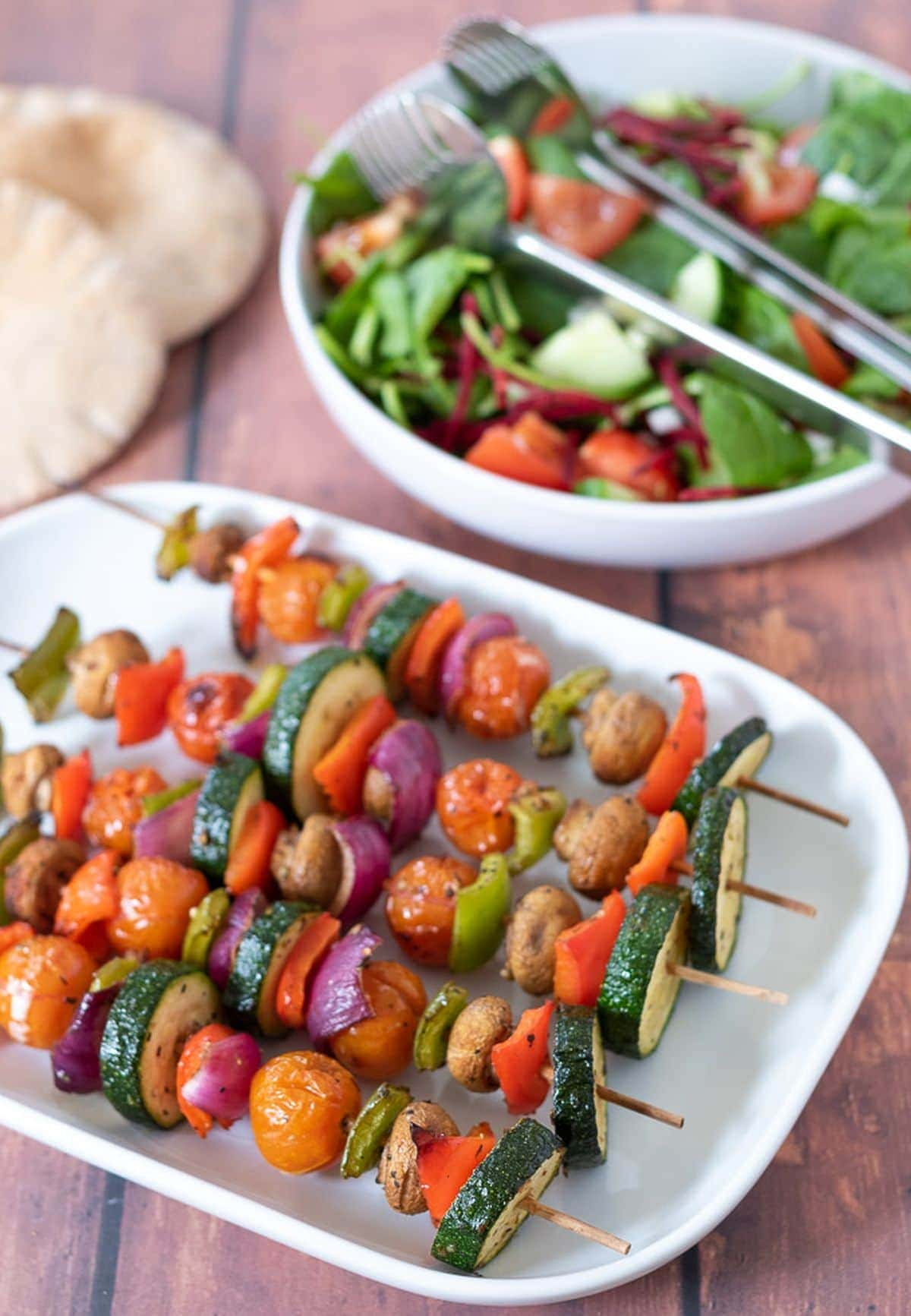 Grilled vegetable skewers laid on a serving dish with a side salad and 2 pita breads in the background.