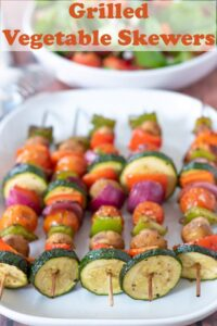 Five grilled vegetable skewers laid on a serving dish. Pin title text overlay at top.